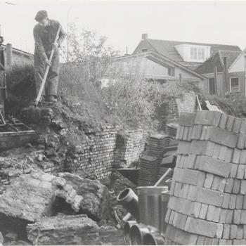 Slopen laatste stukje walmuur oude haven. Links bode Van Os, wiens bestelhuis nog juist boven de muurresten zichtbaar is. Rechts pakhuisgevels aan de Zoutkeetstraat
