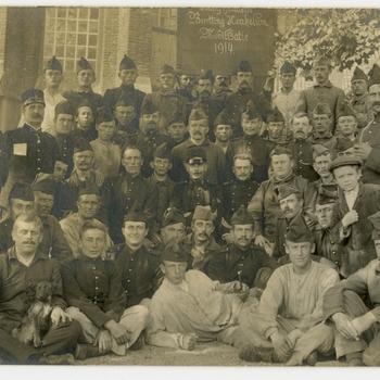 """Een prentbriefkaart van een groep militairen met een vaandel """"Bezetting Heukelum Mobilisatie 1914"""""""