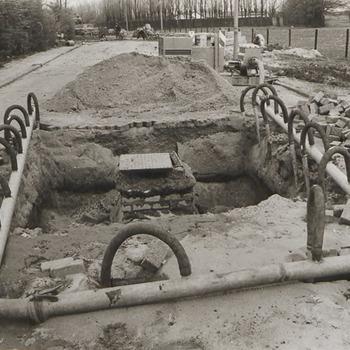 Aanleg nieuwe riolering in Nachtegaallaan. Op de voorgrond een put in het wegdek. Het buizen- en slangenstelsel is aangebracht voor de afwatering van het grondwater, zodat de herstelwerkzaamheden kunnen worden verricht