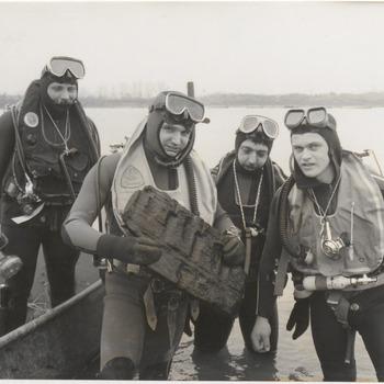 """In de zandafgraving van de firma Mourik aan de Zoelensestraat hebben duikers een brokstuk evt. van een oud Romeins schip opgedoken. Rechts op de foto amateur romeins schipduiker dhr. Toon van Loon met drie andere duikers van het duikteam """"Manta"""" uit Amsterdam"""