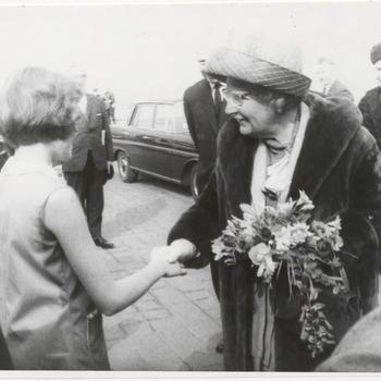 Ontvangst Koningin Juliana bij kerncentrale Dodewaard. In verband met de officiele ingebruikstelling van de eerste Nederlandse Kernenergiecentrale, arriveert Koningin Juliana omstreeks 11 uur in Dodewaard. Hier wordt de Koningin, in gezelschap van haar particulier secretaresse, jonkvrouwe C.E.B. Roell en haar adjudant Kolonel H. van Oordt, begroet door een aantal genodigden, waaronder mr. H.W. Bloemers, commissaris van de Koningin in Gelderland. Op de foto biedt Martien van Erpers Royaards, het elfjarig dochtertje van de directeur van de G.K.N., Koningin Juliana bloemen aan.