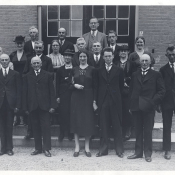Een aantal personen op de stoep van een huis. Achterste rij vlnr: 1. A. Groeneveld, 2. Hn. Van Duijnen, 3. G.E. Landweer, 4. M. de Rooij. Tweede rij vlnr: 1. A.A. J. van Erp, 2. S. v.d. Schans (v.d. Graft), 3. H.K. de Gaaij, 4. N. Vroegindewei, 5. E.S. Brouwers (de Gaaij), 6. Inspecteur Brinkman, 7. G.J. van Hemmen, 8. A.S. Roodzandt (van Hemmen), 8. C. de Groot (de Rooij). Voorste rij vlnr: 1. Hn. Vos, 2. J.E. de Koning, 3. Onbekend, 4. A.S. de Gaaij (van Hemmen), 5. J.W. van Hemmen, 6. A. v.d. Graft, 7. P. Groeneveld.