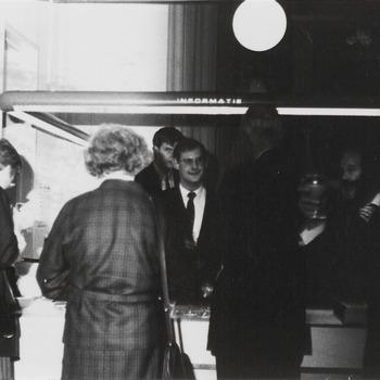 Na de opening van de kerstkaartententoonstelling in de expositieruimte van het streekarchief, worden de bezoekers in de gelegenheid gesteld om de tentoonstelling te bekijken. Aan de balie kan men een drankje nuttigen. Op de foto geheel links mevr. Veerman, uit het midden links dhr. Koops, daarvoor dhr. Merkelbach, man met glas dhr. Houtkoop