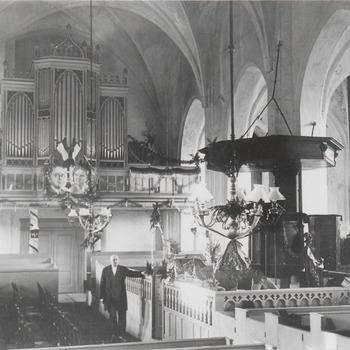 Interieur Ned. Herv. Kerk. De man is koster Hend. van Tricht.