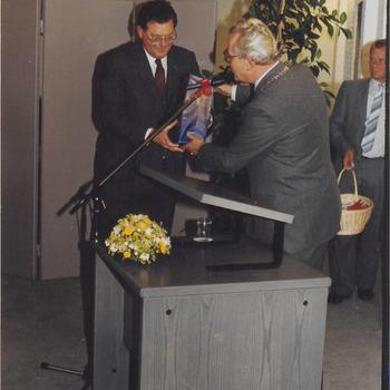 Burgemeester Hommes overhandigd dhr. De Bruijne een geschenk tijdens zijn bezoek aan Buren. Rechts dhr. Lokhorst.
