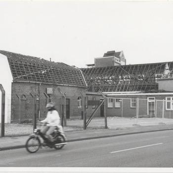 """Koninklijke Maatschappij """"De Betuwe"""" is gelegen aan de Grotebrugse Grintweg. Voordat """"De Betuwe"""" het pand aankocht was hier een boerderij gevestigd van de familie Schoots. Links de stal, rechts de melkslijterij en het woonhuis. Geheel links op de muur van de stal het embleem van de Koninklijke Maatschappij """"De Betuwe"""": Flipje"""