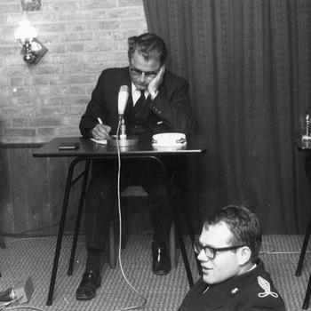 Drie deelnemers aan een quiz? van links naar rechts de heren M. Poulisse, Holtappels en S. de Jong. Ieder voor hun eigen vereniging: voetbalclub DSC, jeugdfanfare Alem en de schaakclub(?). Op de voorgrond de heren Lahey en Van Herwaarden.