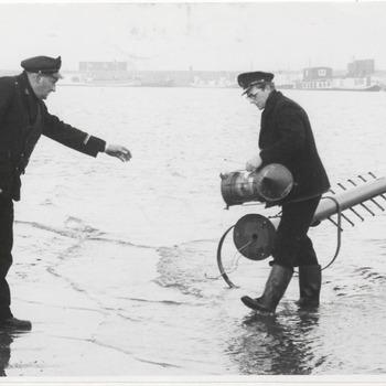 Links dhr. Frans van Dinther, rechts dhr. Van Horssen, in uniform, bezig in de haven met aanbrengen signalering