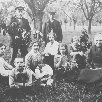 Het gezin Van Ojen gaat eenof tweemaal per jaar in de boomgaard kersen eten. Op de foto eet de familie Van Ojen kersen in de boomgaard van pachter Van Kuilenburg te Zoelen. Staande v.l.n.r.: met tak dhr. A. van Ojen Senior, pachter dhr. Van Kuilenburg. Rij ervoor zittend: C. van Ojen, T. van Ojen. Rij daarvoor zittend: G. van Ojenvan ojenvan Doorn, A.M. van Ojen, R. van Ojen, A.M. van Ojenvan ojen Boudewijn. Voorste rij zittend: jongen: J. van Ojen, meisje: M.A. van Ojen