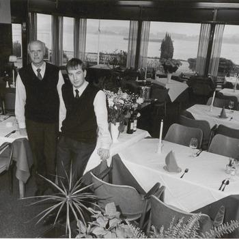Waarschijnlijk een restaurant aan de waal, met twee medewerkers