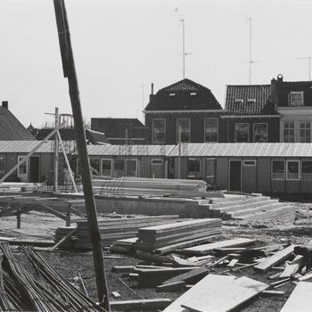 """Bouw schouwburg """"De Agnietenhof"""". Onder het midden de onderbouw van de schouwburg """"De Agnietenhof"""". Rechts uit het midden op de foto de trappen aan de voorkant van de schouwburg, gelegen aan de Kerkstraat. Op de achtergrond de werkketen van het aannemersbedrijf. De straat achter de werkketen is de 1e Bleekveldstraat"""