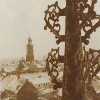 ca.Winters uitzicht over Buren van uit het torentje op het dak van het weeshuis, met rechts een pinakel van het torentje, richting kerk.