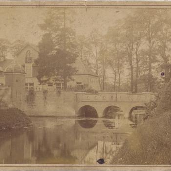 Kasteel Ophemert. In het midden de brug en links het koetshuis van het kasteel. Onder het midden de gracht die rondom het kasteel loopt. Het kasteel staat geheel links van het koetshuis en is niet afgebeeld