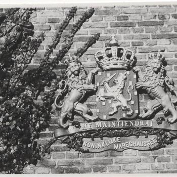 Aan de zijgevel van het weeshuis het wapen van de Koninklijke Marechaussee