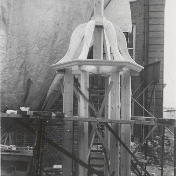 """Hoeveel vakmanschap er in de herbouwde Waterpoort wordt gestopt, bewijst de houten constructie van het torentje dat op het dak van de Waterpoort zal worden geplaatst. Zie het boekje """"Tiel, een versterkte stad"""", fotopagina na blz. 92. Op de achtergrond een gedeelte van het gebouw van het Streekmuseum"""