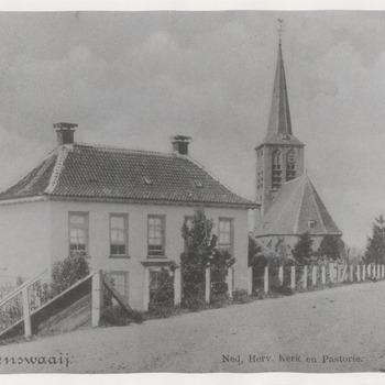 N.H.-kerk met pastorie op voorgrond