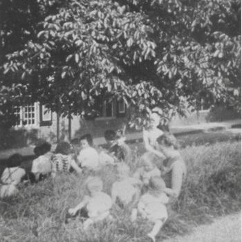 Kinderen uit het weeshuis in het gras op de Wal voor het Weeshuis.