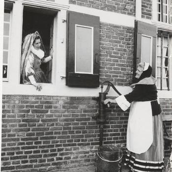 Vrouw in Middeleeuwse kleding bij een pomp voor een oud huis, in het venster een jonge vrouw, adellijke uitstraling