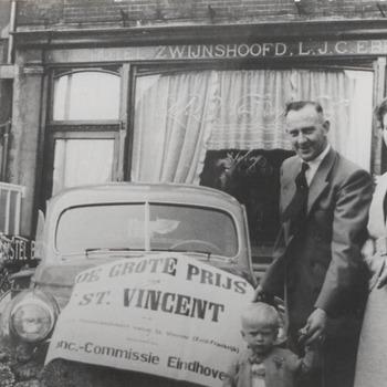 """Winnaar duivenwedvlucht """"De grote prijs van St. Vincent"""" dhr. A. van Zandwijk (in het midden). Links dhr. van Zandwijk, rechts mevr. van Zandwijk-Faassen. Op de achtergrond Hotel Zwijnshoofd aan de Varkensmarkt"""