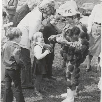 """Reclame Koninklijke Mij. """"de Betuwe"""" Flipje . Als Flipje verkleed kind, reclame makend voor de jamfabriek op de Waalkade. Op de achtergrond de Waalstraat"""