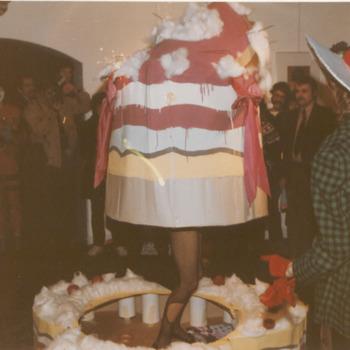 Opening freak-festival I Groote Societeit. In het Streekmuseum de Groote Societeit wordt het Freak-festival geopend met een papieren taart waaruit een vrouw tevoorschijn springt. Op de foto is de taartfreak-festivalbewoonster bezig uit haar omhulsel aan het komen