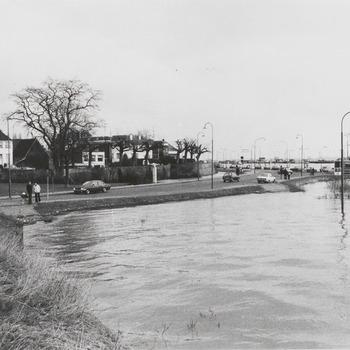 Waalstraat hoge waterstand Waal, het water staat tot aan de straat , de parkeerplaats staat helemaal onder