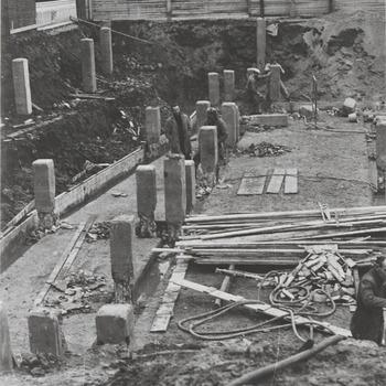 """Bouw schouwburg """"De Agnietenhof"""". Een gedeelte van de fundering van schouwburg """"de Agnietenhof"""" in aanleg. Geheel op de achtergrond links is een gedeelte van het Gerechtsgebouw zichtbaar. Het gebouw links op de foto, voor de auto, is het Arbeidsbureau. De huizen geheel rechts op de achtergrond zijn gelegen aan de Hucht"""