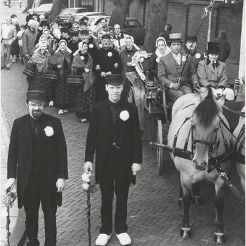 """Een Tielse dansschool houdt een themadag. Twee echtelieden in spe, Johan Vermeeren en Coby Nolber, die pas echt over veertien dagen trouwen, """"trouwen"""" nu in oude stijl, zelfs voorafgegaan door twee """"aanzeggers"""". De folkloregroep de Schaddenrieders uit Enschede verleent medewerking. De ambtenaar van de burgerlijke stand is een van de leden van deze groep"""