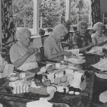 """Blz. 31./Blz. 25. """"Ouderenwijzer"""", handwerkclubje in bejaardenhuis Oranjehof te Buren. Van links naar rechts, mevr. van Toorn, mevr. van Toorn, mevr van Arnhem en mevr Sies,"""