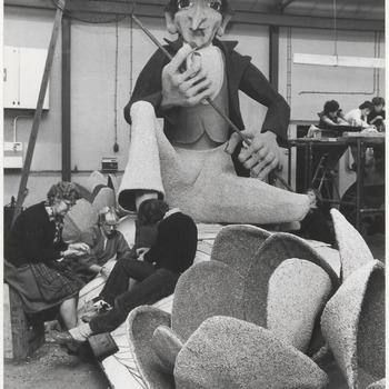 Vrijwilligers bezig met het plakken voor het fruitcorso, een figuur is al zichtbaar.