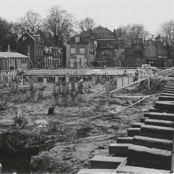 """Bouw schouwburg """"De Agnietenhof"""". Op de voorgrond de aanleg van de fundering van schouwburg """"de Agnietenhof"""". Op de achtergrond de onderbouw van de schouwburg. Rechts uit het midden op de foto zijn timmerlieden bezig met het maken van de bekisting voor de onderbouw. Geheel achteraan de Kerkstraat. De huizen links achter de werkketen zijn gelegen aan de 1e Bleekveldstraat. De huizen rechts ervan zijn gelegen aan de Achterweg"""