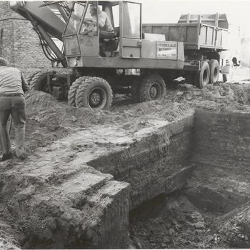 De herbouw van de historische Waterpoort aan het Plein is een paar dagen geleden begonnen. Op de foto is men met graafwerkzaamheden ten behoeve van de fundering van de Waterpoort bezig. De bouw van de Waterpoort kost 1,2 miljoen gulden en zal een jaar in beslag nemen