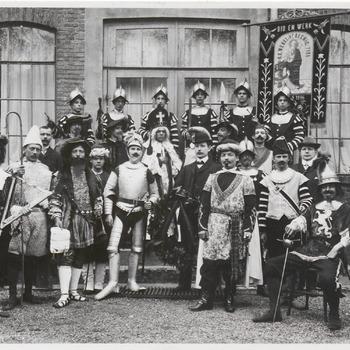 Toneelspelers, uitgedost als ridders, adel, maar ook in moderner kostuum, staan voor gebouw