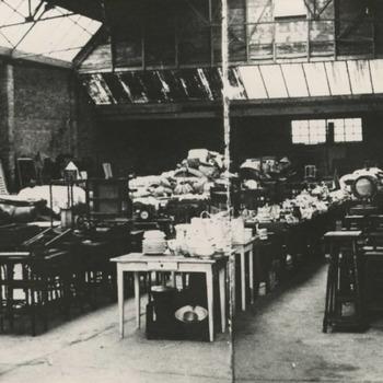 """Interieur van de opslagplaats """"H.A.R.K."""", (Hulpactie Rode Kruis). De hulpgoederen zijn bestemd voor lieden die in de oorlog hun bezittingen zijn kwijtgeraakt"""