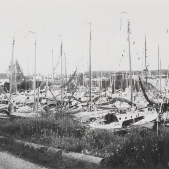 """De zeilboten die meedoen aan de Tiel-Merwederace liggen in de Nieuwe Haven. Geheel links het clubhuis van zeilvereniging """"De Waal"""". De foto is gemaakt enige uren voordat de zeilrace begint"""