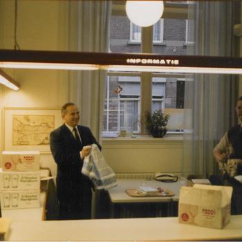Achter de balie van het Stadsarchief van Tiel worden voorbereidingen getroffen voor de viering van het 25 jarig jubileum van het Streekarchivariaat Tiel-Buren-Culemborg. V.l.n.r.: bode Wittekamp, archivaris Hein Merkelbach, archiefmedewerker Bram Boeren
