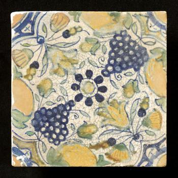 Tegel van keramiek, tinglazuur, voorstellende een rozet met naar binnen gerichte tulpen en druiven gemaakt in Zuid-Holland ca. 1600-1625