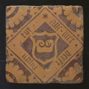 vloertegel van aardewerk en een decoratie in slibtechniek, met opschrift, ca. 1525-1575