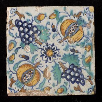 Tegel in tinglazuur, rozet met granaatappels en druiven, gemaakt in Nederland ca. 1600-1625