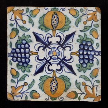 Tegel in tinglazuur, voorstellende leliedecor met granaatappels en druiven, vervaardigd te Nederland ca. 1600-1625