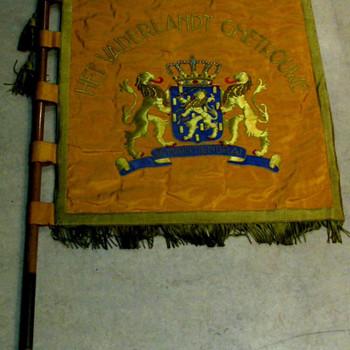 Vaandel, van katoen en velours, op houten vaandelstok met leren draagfoudraal, op vaandel een afbeelding van de Nederlandse leeuw