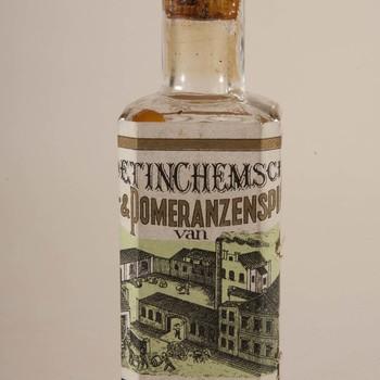 Fles met schenkdop en inhoud met etiket waarop tekst 'Perlstein Elixer'