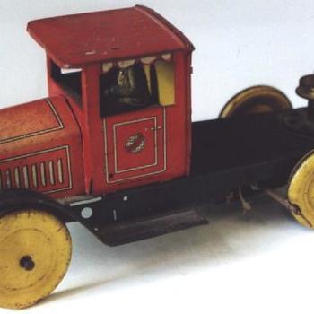 vrachtauto. Zwarte platte bak en rode cabine met mannetje. Opwindmechanisme op de achterwielen. Kinderspeelgoed, 1900-1925.