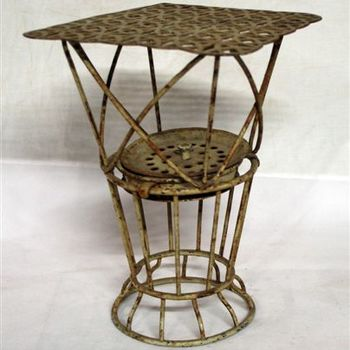 luierbaker. Korfvormig model met voetstuk gemaakt van metaaldraad. Opbouw afgedekt met metaal. Kinderspeelgoed. Periode 1900-1925.