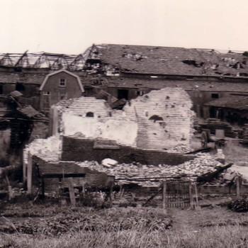 Vernielde steenfabriek met huizen.