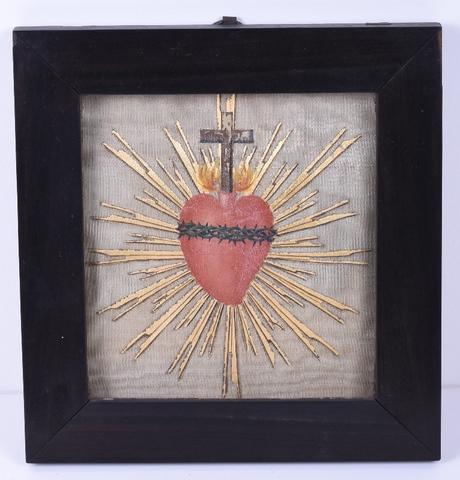 Brandend hart omgeven door stralenkrans, bovenop een kruis