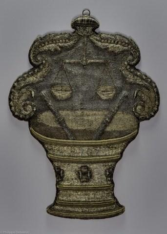Wapenschild van het ambacht van de Gentse kruideniers, kaaskopers en kaasgieters, met de voorstelling van een vijzel met twee stampers waarboven een weegschaal