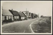 links woningen aan asfaltweg, rechts gras en struiken