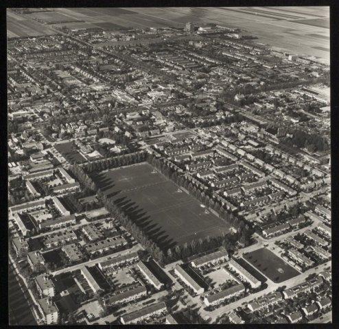 Luchtfoto van het zuidelijk deel van Nieuw-Vennep met in het midden de voetbalvelden van DIOS en rechts de Bols fabrieken.