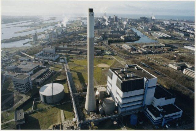 Luchtfoto met op de voorgrond de electriciteitscentrale UNA met aansluitend het bedrijfsterrein van Hoogovens Staal.